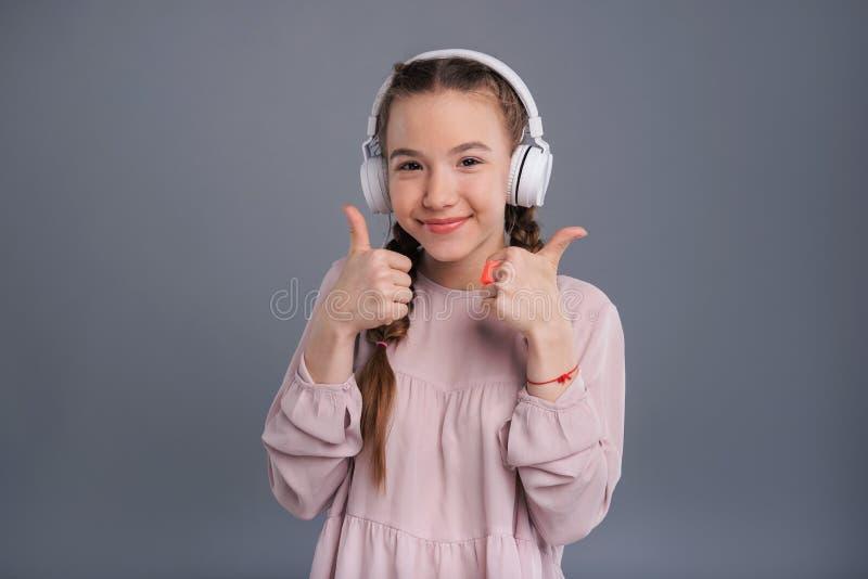 Adolescente mignonne écoutant la musique et montrant des pouces- image stock