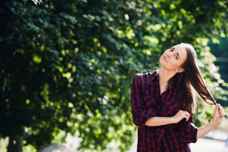 Adolescente mignonne dans le tenue décontractée jouant avec ses tresses, regardant l'appareil-photo et le sourire, se tenant cont photo stock