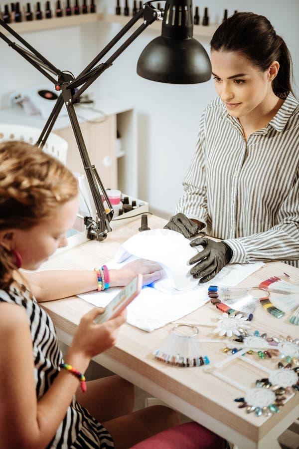 Adolescente moderne à l'aide de son smartphone tout en rendant visite à l'artiste de clou image libre de droits