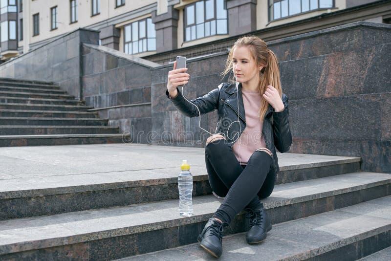 Adolescente moderno de la chica joven que descansa sobre las escaleras mientras que camina alrededor de la ciudad El concepto de  imagen de archivo libre de regalías