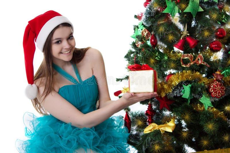 Adolescente na árvore de Natal inferior atual de oferecimento do chapéu de Santa fotografia de stock royalty free