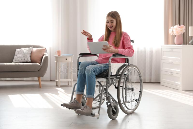 Adolescente na cadeira de rodas usando o bate-papo video na tabuleta fotos de stock royalty free