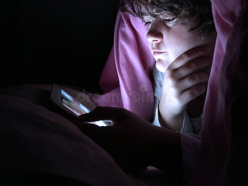 Adolescente na cama na cama na noite, usando um dispositivo digital imagens de stock royalty free