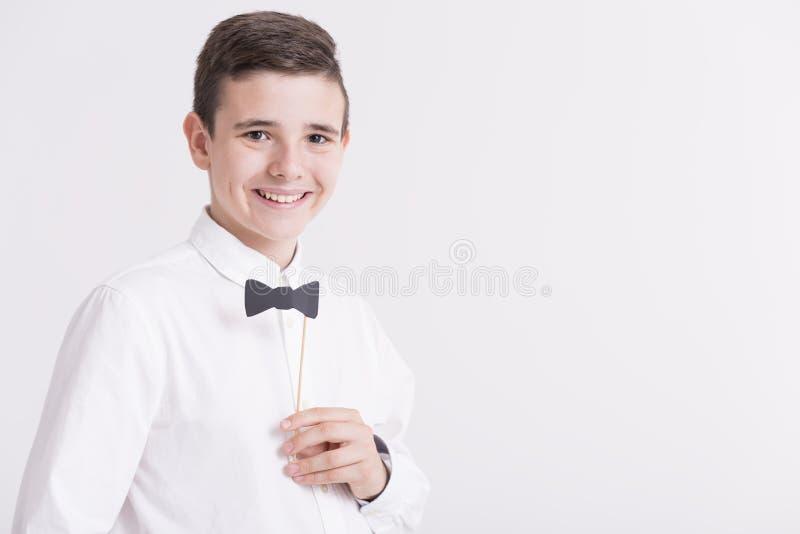 Adolescente na camisa branca elegante com curva de papel do juntamento fotos de stock royalty free