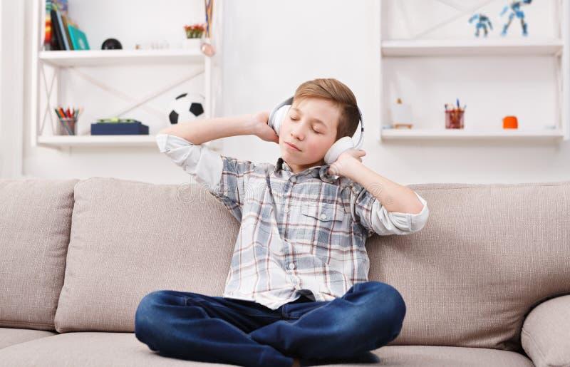 Adolescente na música de apreciação ocasional nos fones de ouvido em casa imagens de stock royalty free