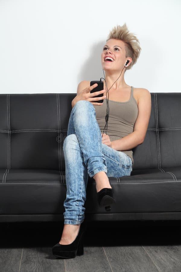 Adolescente na moda que escuta a música em casa imagem de stock royalty free