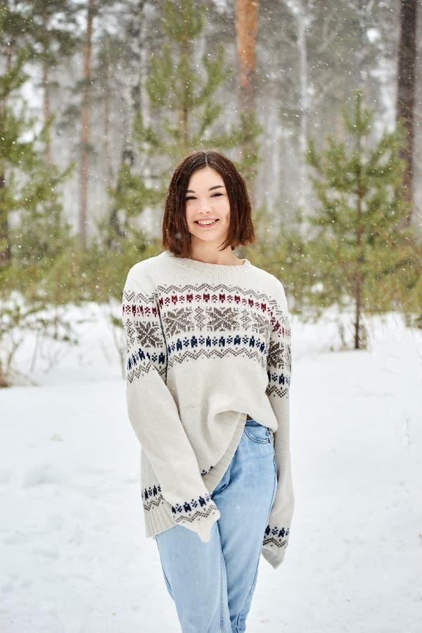Adolescente na queda de neve da floresta do inverno fotos de stock royalty free