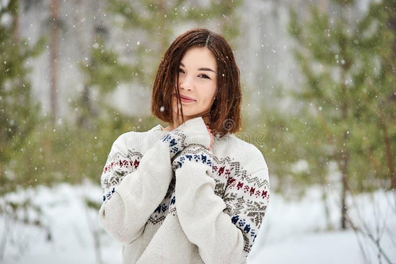 Adolescente na queda de neve da floresta do inverno fotografia de stock