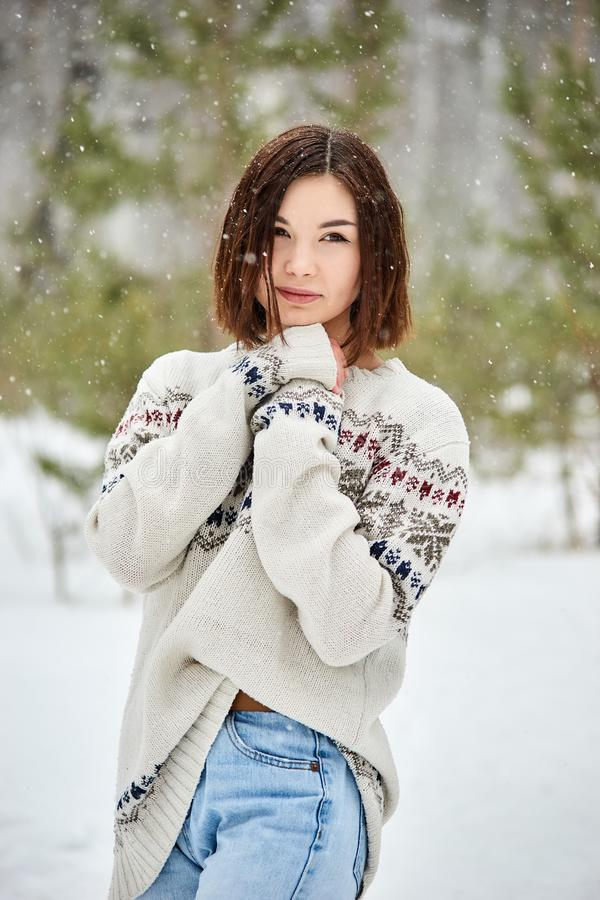 Adolescente na queda de neve da floresta do inverno fotos de stock