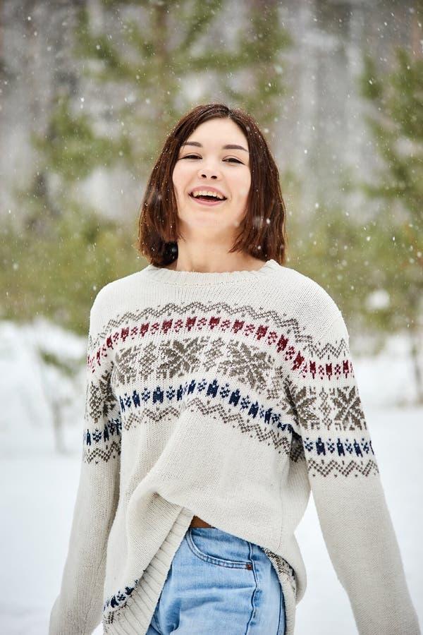 Adolescente na queda de neve da floresta do inverno foto de stock royalty free
