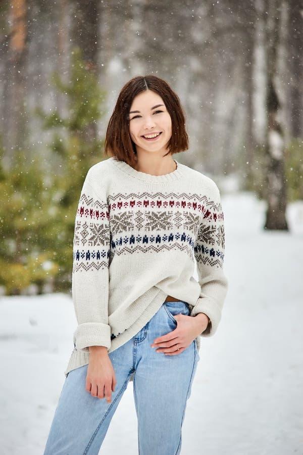 Adolescente na queda de neve da floresta do inverno fotografia de stock royalty free