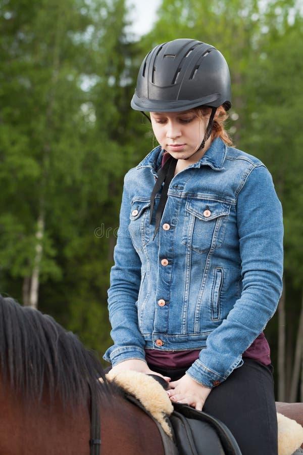 Adolescente nel cavallo nero di giri del casco fotografie stock libere da diritti