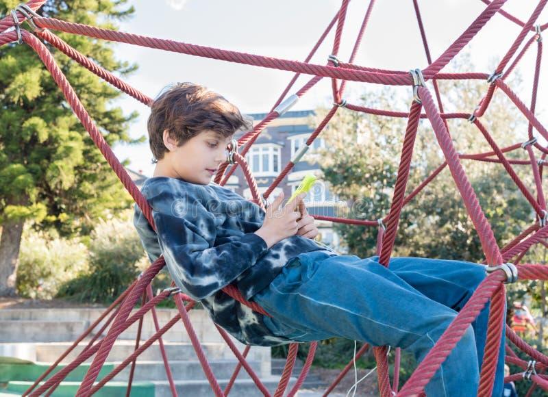 Adolescente nel telaio di scalata facendo uso dello Smart Phone fotografia stock libera da diritti