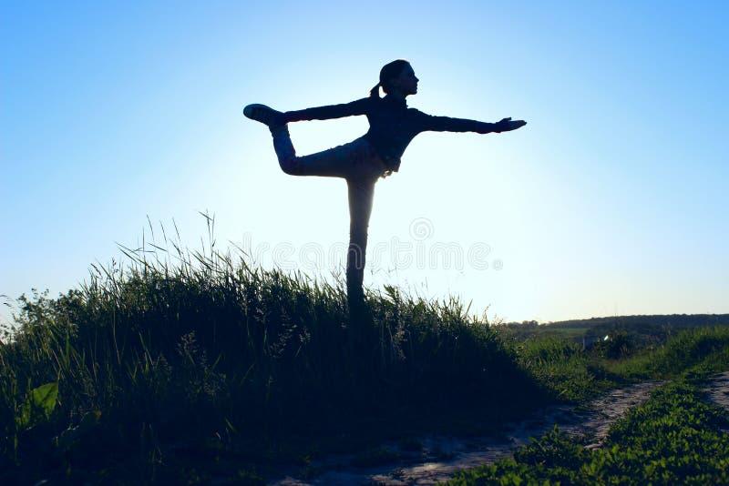 Adolescente nella posizione d'equilibratura di yoga di A Ragazza all'aperto Yoga di forma fisica Allungamento della donna fotografia stock libera da diritti