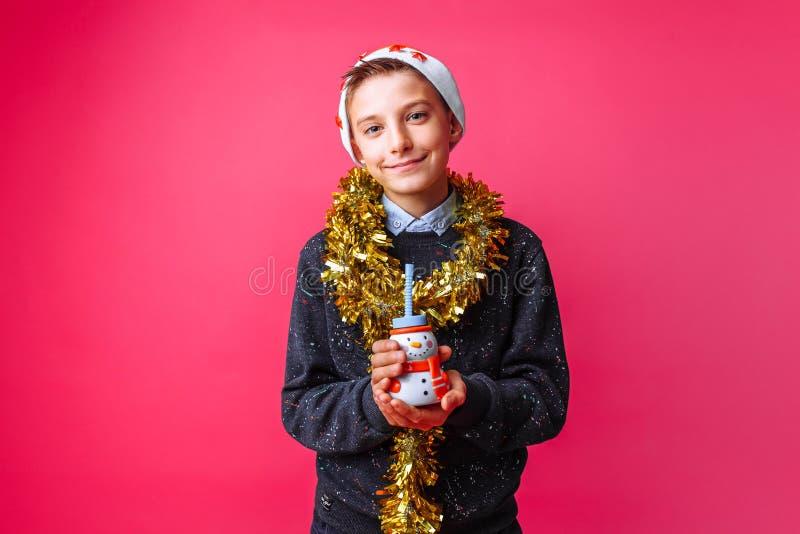 Adolescente no chapéu Santa Claus e no ouropel no pescoço, guardando uma BO imagem de stock