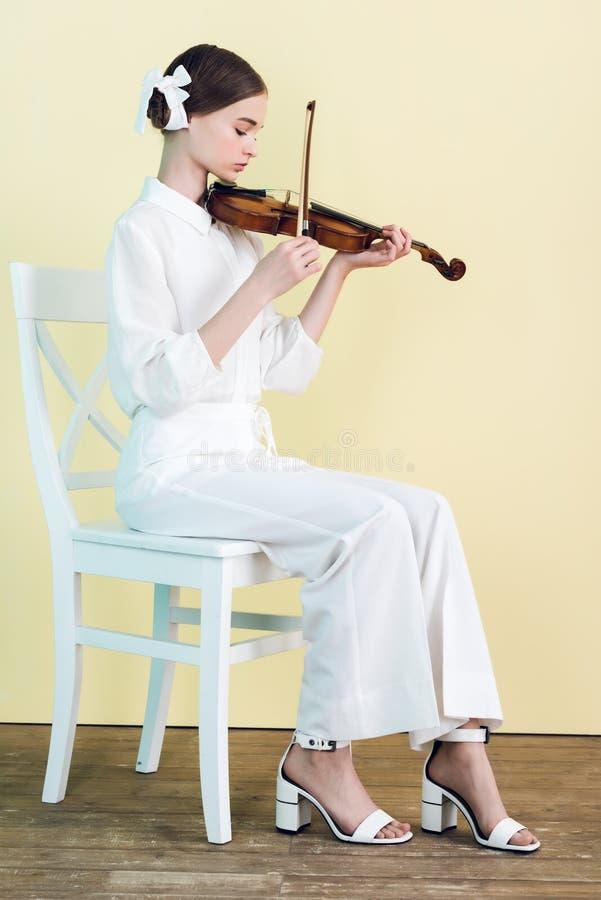 adolescente no equipamento branco que joga o violino e o assento foto de stock