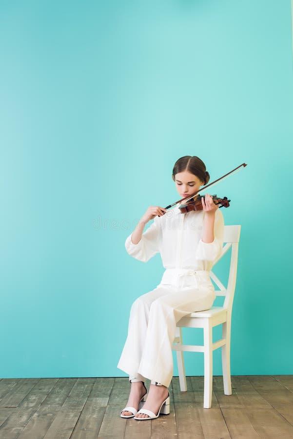 adolescente no equipamento branco que joga o violino e que senta-se na cadeira fotografia de stock royalty free