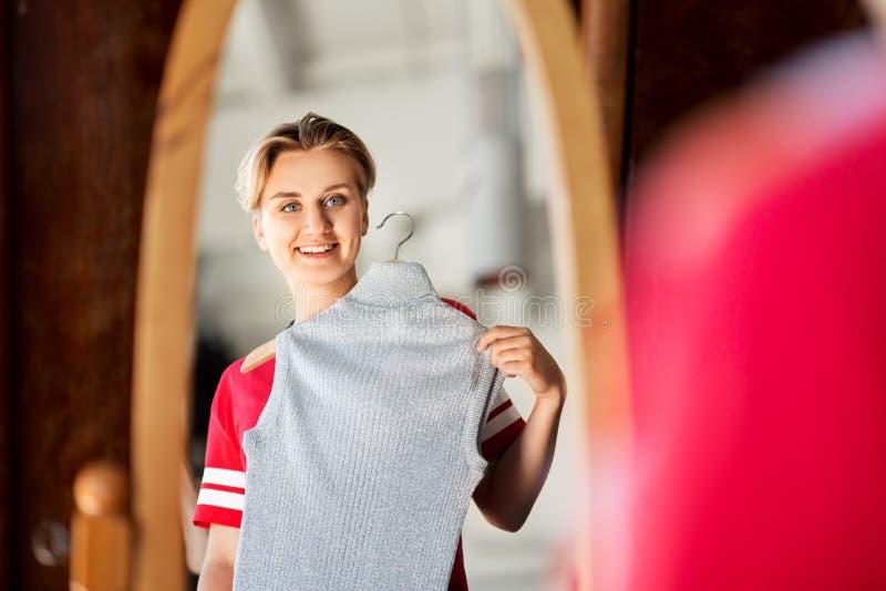 Adolescente no espelho da loja de roupa do vintage foto de stock