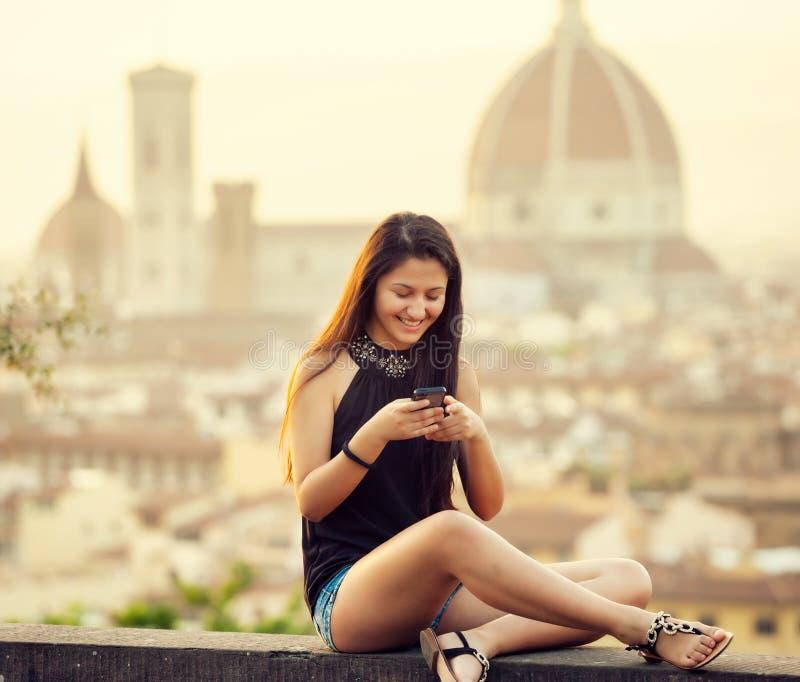 Adolescente no por do sol em Florença usa o smartphone imagens de stock