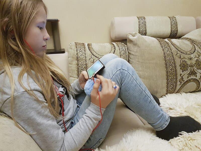 Adolescente no sofá no smartphone dos fones de ouvido imagens de stock
