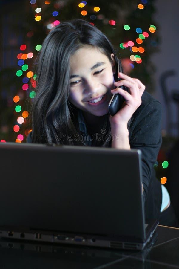 Adolescente no telefone do portátil e de pilha fotografia de stock