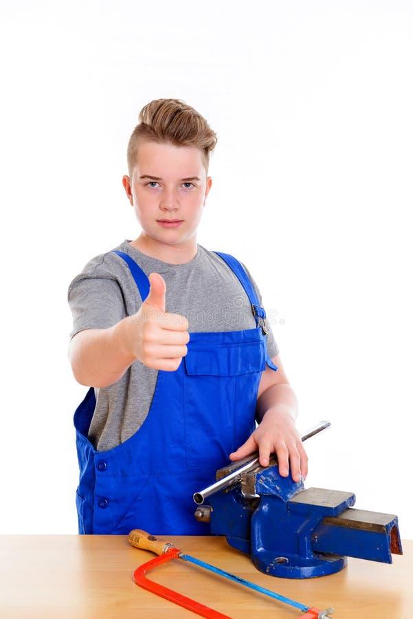 Adolescente no treinamento profissional com serrote e polegar acima foto de stock royalty free
