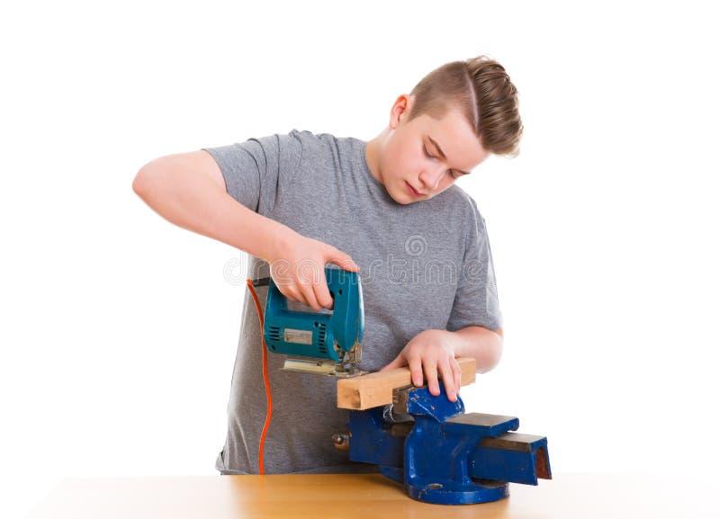 Adolescente no treinamento profissional usando o padsaw imagens de stock
