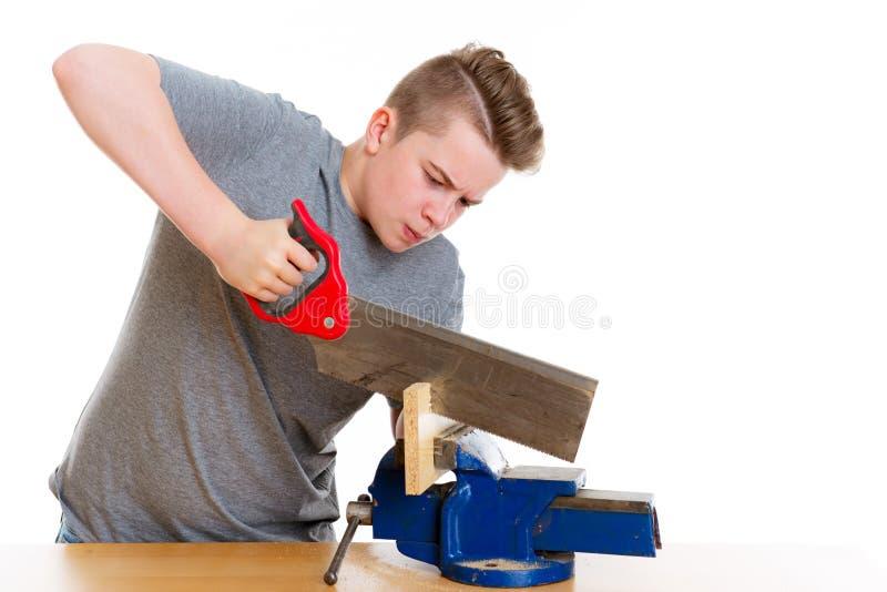Adolescente no treinamento profissional usando a serra da mão imagens de stock royalty free