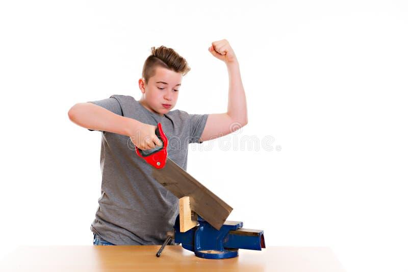 Adolescente no treinamento profissional usando a serra da mão imagens de stock