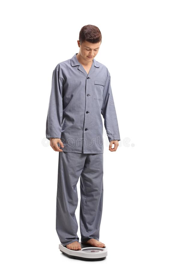 Adolescente nos pijamas que estão em uma escala do peso imagens de stock royalty free