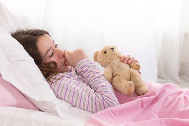 Adolescente novo adormecido na cama com Teddy Bear fotos de stock