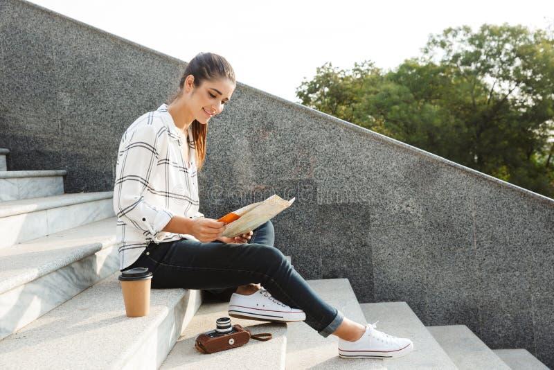 Adolescente novo alegre que senta-se em uma escadaria foto de stock royalty free