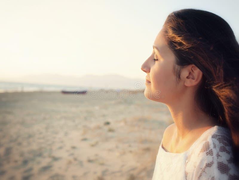 Adolescente novo bonito com um vestido branco na praia em sóis imagens de stock royalty free