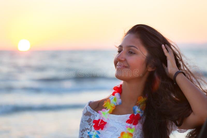 Adolescente novo bonito com um vestido branco na praia em sóis foto de stock