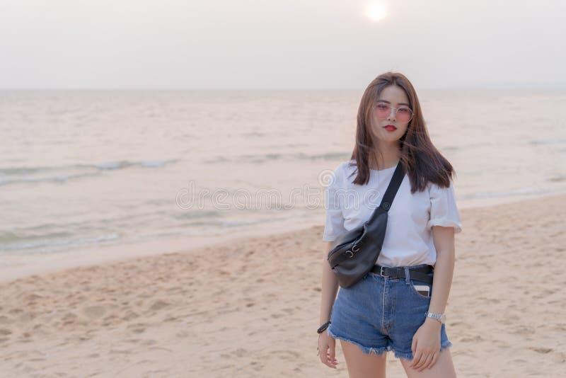 Adolescente novo fêmea bonito asiático que relaxa na praia para trás foto de stock