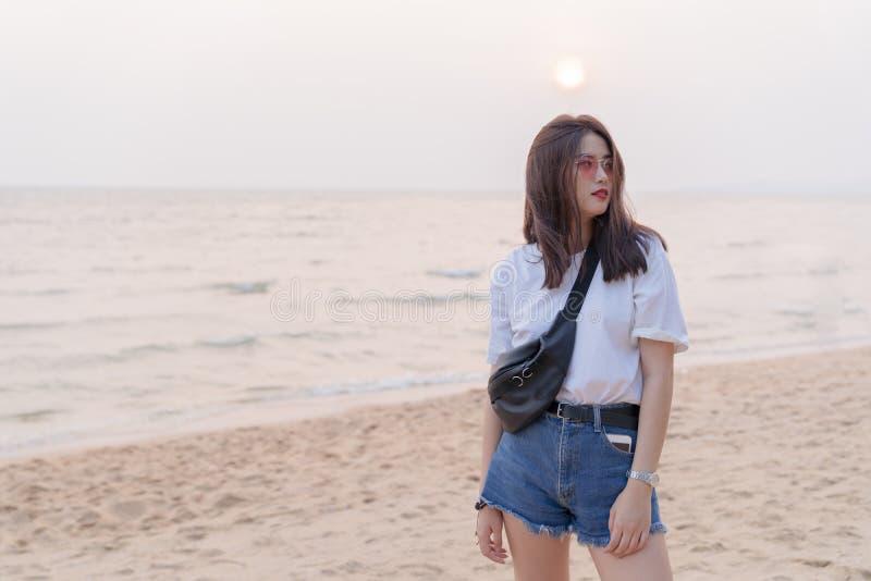 Adolescente novo fêmea bonito asiático que relaxa na praia para trás fotografia de stock