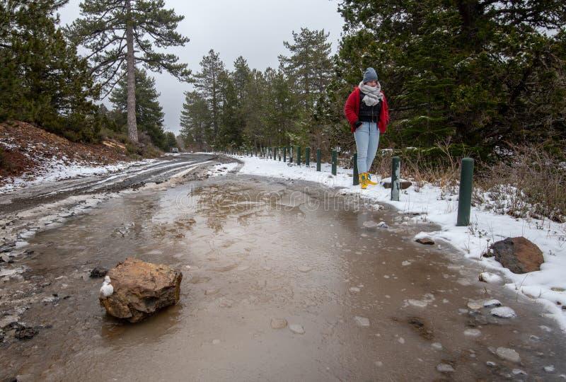 Adolescente novo que anda em uma estrada congelada em montanhas de Troodos em Chipre imagem de stock
