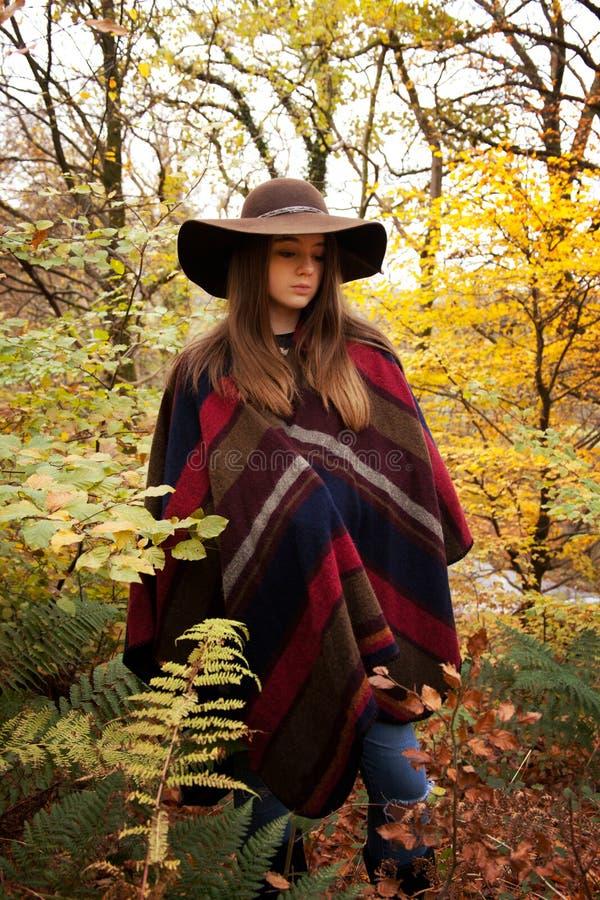 Adolescente novo que está em uma floresta no outono foto de stock royalty free