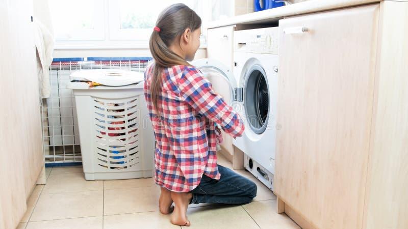 Adolescente novo que faz trabalhos domésticos na lavandaria fotos de stock royalty free