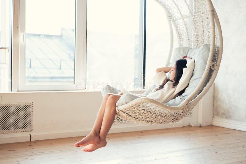 Adolescente novo que relaxa na cadeira de suspensão confortável perto da janela em casa Criança que senta-se na cadeira e que ref fotografia de stock royalty free