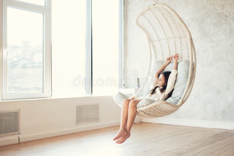 Adolescente novo que relaxa na cadeira de suspensão confortável perto da janela em casa Criança que senta-se na cadeira e que ref foto de stock