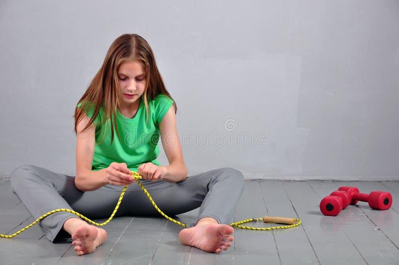 Adolescente novo que sentam-se no assoalho com corda de salto e pesos que relaxam tendo o resto no estúdio fotografia de stock royalty free