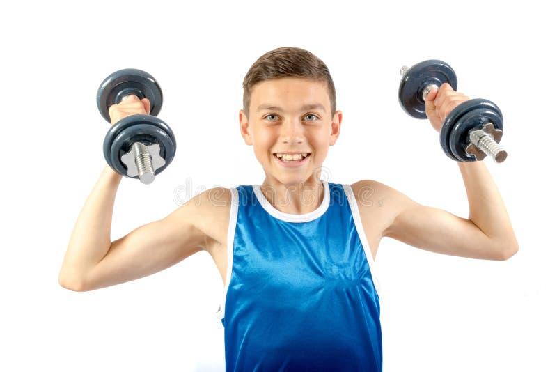 Adolescente novo que usa pesos foto de stock