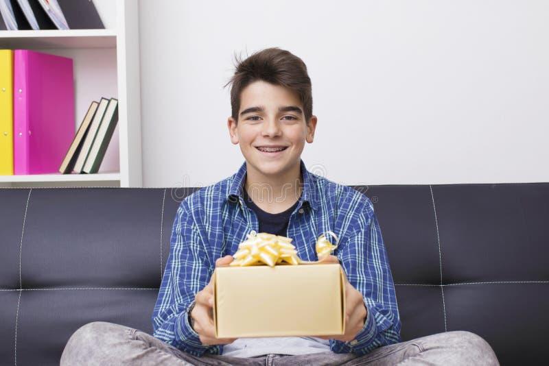 Adolescente o preadolescente con la caja de regalo de la Navidad foto de archivo libre de regalías