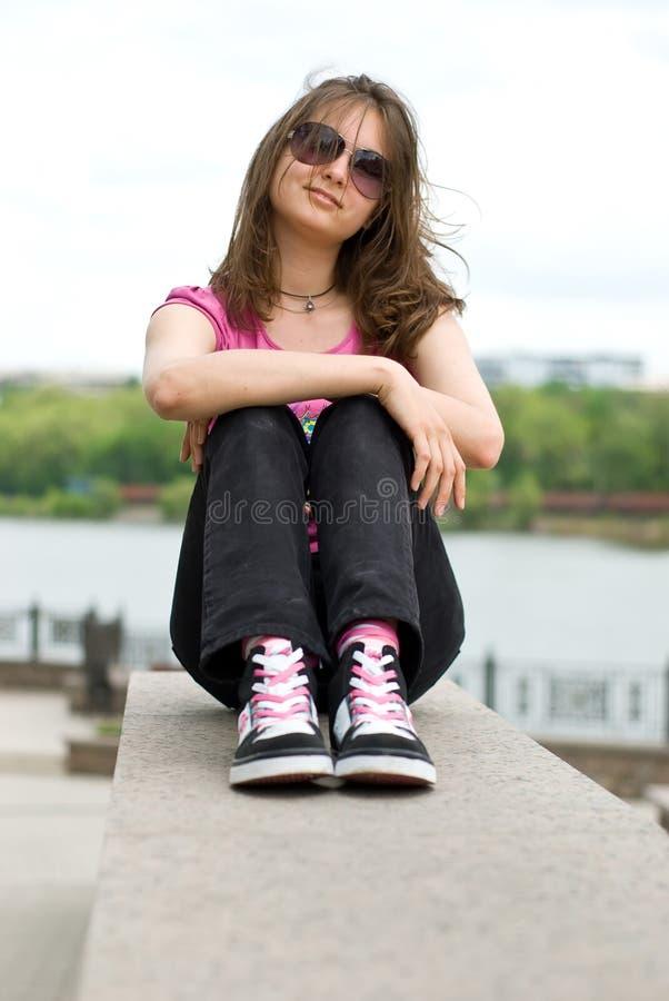 Adolescente in occhiali da sole e scarpe da tennis fotografia stock