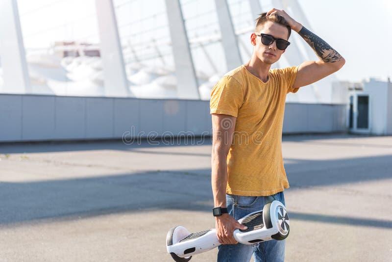 Download Adolescente Ordenado Que Mantiene Hoverboard Brazo Foto de archivo - Imagen de asimiento, atlético: 100533132
