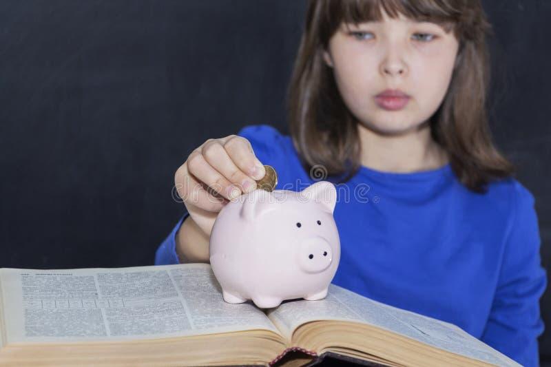 Adolescente p?e moedas no mealheiro O conceito de educa??o paga foto de stock