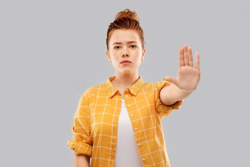 Adolescente pelirrojo que hace la detención de gesto fotografía de archivo libre de regalías