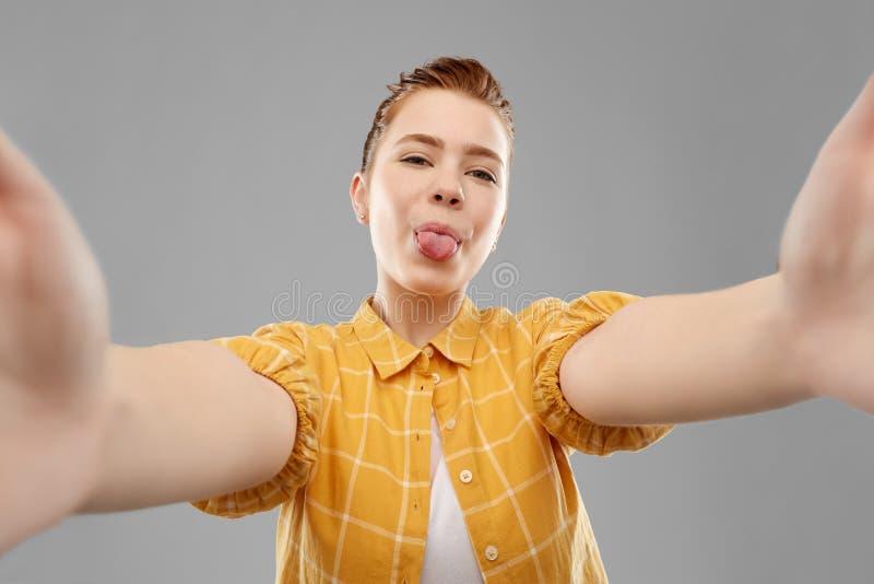 Adolescente pelirrojo que toma el selfie con la lengua fotografía de archivo