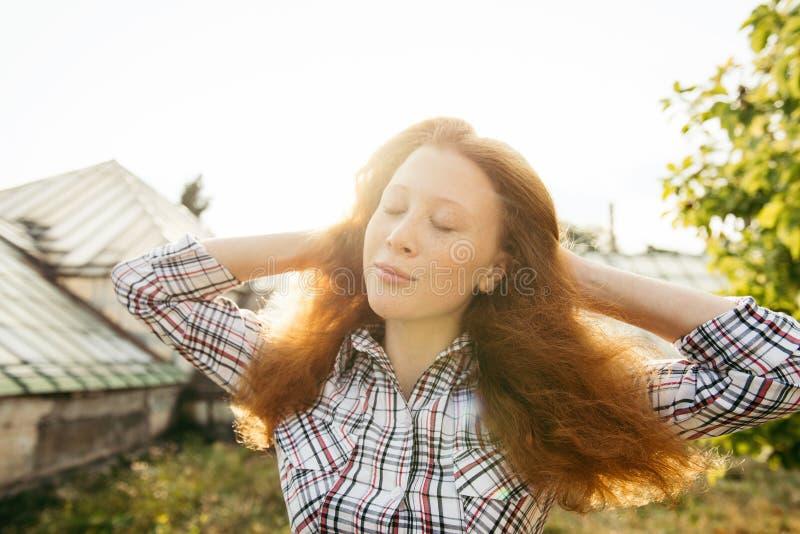 Adolescente pelirrojo sobre la luz del sol al aire libre que se relaja fotografía de archivo